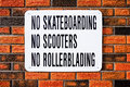 No skateboarding no scooters no rollerblading sign on red brick wall Royalty Free Stock Photo