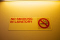 No smoking in lavatory sign warning in a toilet on airplane Royalty Free Stock Photo