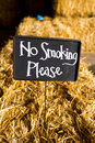 No smoking please sign a chalkboard at a wedding reception reads and is placed on a hay bail Royalty Free Stock Photography