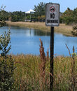 No swimming at local park sign beside lake with picnic area in background Stock Images