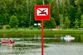 No swimming sign a danger at the beach there are distance pedal boats Royalty Free Stock Photo