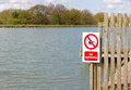 No swimming sign on jetty at edge of lake Royalty Free Stock Image