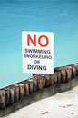 No swimming sign by the ocean that says snorkeling or diving into water Royalty Free Stock Photo