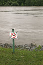 No swimming sign posted at edge of picnic area on riverbank Stock Image