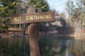 No swimming sign rustic wooden shown at a mountain lake in autumn reminiscent of a cross Stock Photo