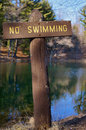 No swimming sign rustic wooden shown at a mountain lake in autumn reminiscent of a cross Royalty Free Stock Image