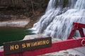 A no swimming sign with waterfall in the background Royalty Free Stock Photography
