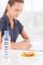 No time for lunch beautiful young woman writing something in her note pad while sandwich and a bottle of water laying on Stock Photo