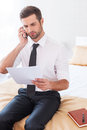 No time for rest confident young man in shier and tie talking on the mobile phone and holding document while sitting on the bed in Royalty Free Stock Image