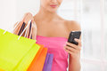 No time for talking cropped image of beautiful young woman in pink dress holding shopping bags and mobile phone Stock Images