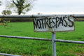 No trespass sign with the words painted on it and hanging on fence Royalty Free Stock Photography