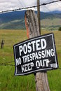 No trespassing sign on a old rustic wood post with rural background Royalty Free Stock Images