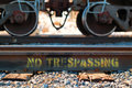 No trespassing written on tracks with train wheels on top Royalty Free Stock Images