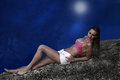 Nocturnal woman by sea coast in moon light tranquil beauty Royalty Free Stock Image