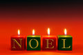 Noel candles that spell the word burning against a red graduated background Royalty Free Stock Photography