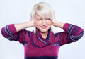 Noise young woman in woolen sweater protecting ears from Stock Photos