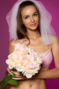 Noiva sexy bonita com cabelo escuro longo em um véu branco roupa interior cor de rosa do laço com o ramalhete de pálido pe nias Imagem de Stock