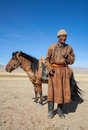Nomad with his horse faithful in the steppes of mongolia Royalty Free Stock Photography