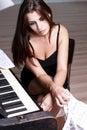 在钢琴附近的哀伤的女孩 免版税库存照片