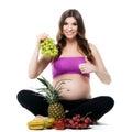 χαμογε ώντας έγκυος γυναίκα με τα φρούτα σε ένα άσπρο υπόβαθρο Στοκ Εικόνες