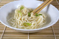Noodles in broth in white bowl of chinese with green onion and chopsticks on bamboo mat Stock Images