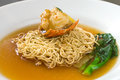Noodles with lobster chinese noodle dish of fried egg in rich clear gravy topped in shell and accompanied green vegetable Royalty Free Stock Images