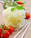 Noodles rice twisted with oil and vegetables on sacking tomatoes different pepper in carafe chopsticks a background of sack cloth Stock Photos