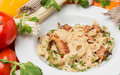 Noodles with vegetables and garnish on white plate hot Stock Photography