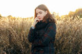 Noon portrait young beautiful redhead woman in scarf and plaid jacket on faded meadow cold season outdoors thoughtful Stock Image