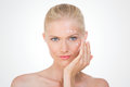 Nordic girl applying salve on her face blond woman testing cream cheekbone and front grey background Royalty Free Stock Image