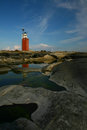 Nordic lighthouse scenic view of a island with a rocky landscape and water reflections in foreground Stock Photography