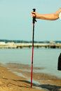 Nordic walking stick in female hand on a sandy beach active mature lifestyle senior sea shore Stock Photography