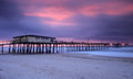 North carolina fishing pier at sunrise the frisco damaged by past storms on the outer banks of the cape hatteras national seashore Stock Photography