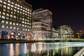 North dock in londons docklands at night london united kingdom november illuminated modern buildings london s canary wharf is one Royalty Free Stock Photo