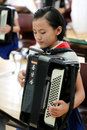 North korea a charming schoolgirl was playing the accordion in pyongyang children s palace attaches great importance to students Stock Photo