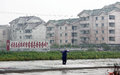 North korea sinuiju here is streetscape in the rain gray building political slogans and lonely pedestrian Royalty Free Stock Photography
