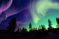 Northern lights aurora borealis in the night sky over beautiful lake landscape