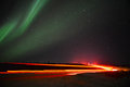 Northern lights common name aurora borealis polar aurorae northern hemisphere slow shutter speed vehicle tail lights traveling Royalty Free Stock Photo
