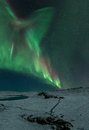 Northern lights on with a corona nothern dancing above the wilderness in iceland stretching from the horizon to in the top left Royalty Free Stock Photography