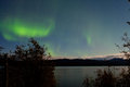 Northern lights moon lit clouds over lake laberge band of green aurora borealis on night sky with and stars boreal forest taiga of Stock Photography