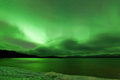 Northern lights night sky over frozen lake laberge green sparkling show of aurora borealis or on cloudy winter scene of yukon Royalty Free Stock Photos