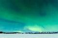 Northern lights over moon lit frozen lake laberge intense or aurora borealis or polar on night sky winter landscape of yukon Stock Image