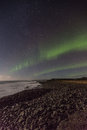 Northern lights by the sea or aurora borealis dancing in sky below shore in iceland Stock Photos