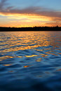 Northern wisconsin lake sunset sunlight reflects off ripples of sweeney in Royalty Free Stock Images