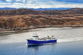 Norwegian fish carrier ship blue passes through the fjord Royalty Free Stock Photography
