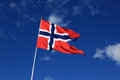 A norwegian flag blowing in the wind against blue sky with cloud clouds Stock Photography
