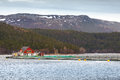 Norwegian floating fish farm with red wooden house traditional and nets Royalty Free Stock Photo