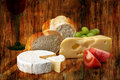 Norwegian jarlsberg and camembert with italian white bread on wooden cutting board Stock Image
