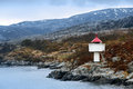 Norwegian lighthouse white tower with red top stands on coastal rocks Stock Photography