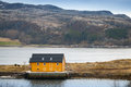 Norwegian village with yellow house on coast wooden sea Royalty Free Stock Photography